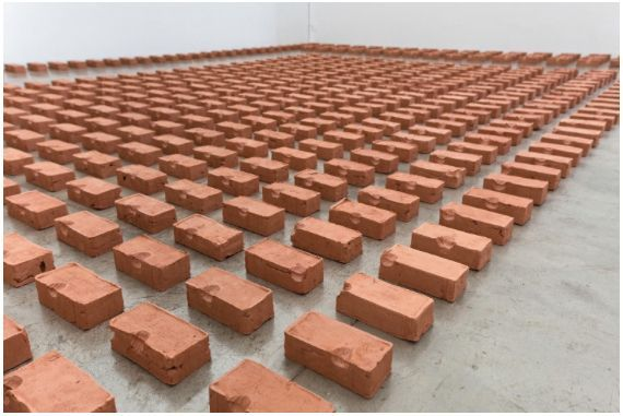 "View of the exhibition ""Sirvete de mi, sirveme de ti"", Proyecto Amil, Lima, Peru,  2016""Here eating Dirt Mom…"", 2014 / An installation composed of more than 1,200 clay bricks made by Argote in Brazil"