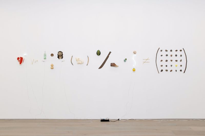 """Nueve - from the series Reducción objetiva orquestada (2015-2020),"" 2017, brass, branches, neon, stones, glass, ceramic, clay, baseball ball, machete, wild boar skull, reed snakes, golf ball, wood, iron, porcelain, dry calabash, 64.8 x 431.8 x 10 cm (25 1/2 x 170 x 3 15/16 inches)"