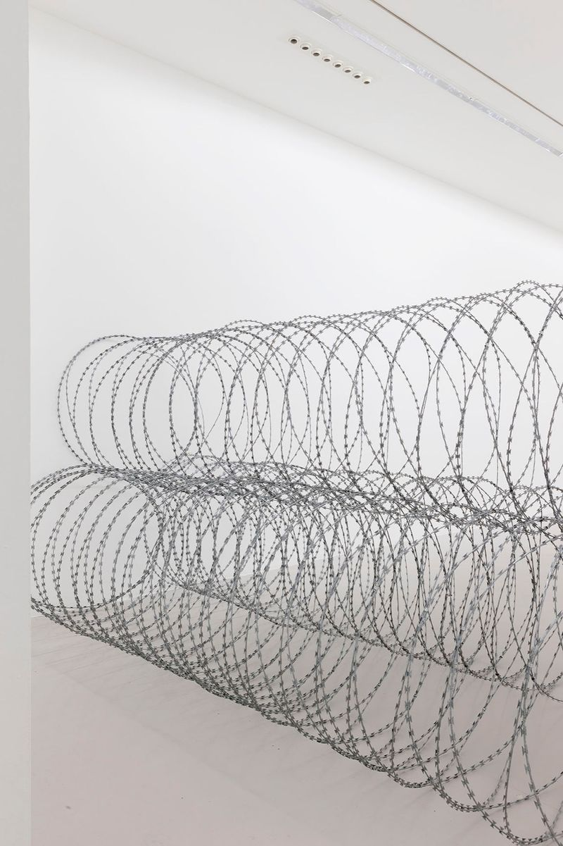 """View of the exhibition Draft at Galerie Perrotin - Saint Claude  Paris (France), 2015 """"Draft - 2"""", 2015 / razor barbed wire / 200 x 460 x 140 cm; 78 3/4 x 181 1/8 x 55 1/8 in / Unique (From a series of three unique works - produced in variable dimensions according to the actualization)"""